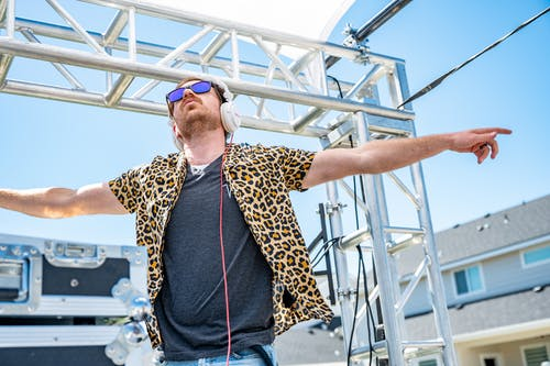 Trendy young man in headphones dancing on stage during music festival