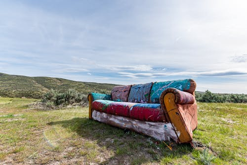 Old abandoned sofa with colorful paints placed on grassy terrain near green hills on sunny day
