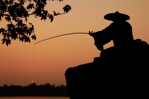 Silhouette Photo of Person Wearing Hat Holding Fishing Rod