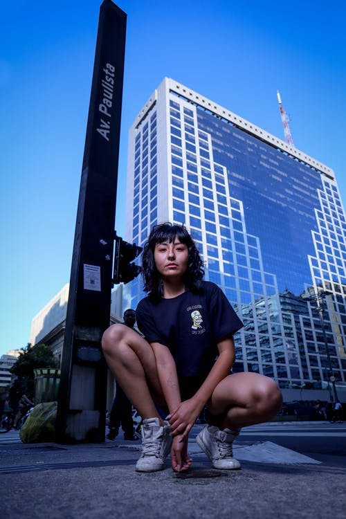 Stylish ethnic young woman squatting on street in downtown