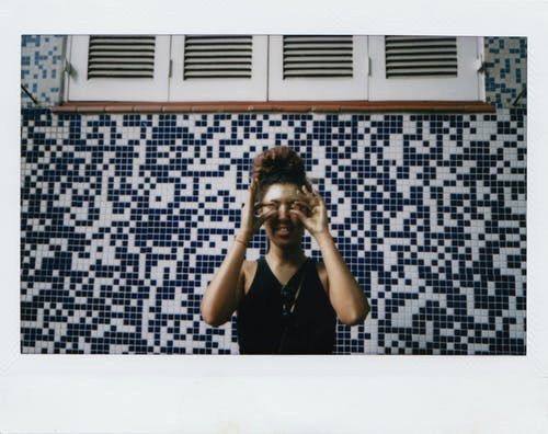 Young ethnic female in casual clothes smiling while standing against geometric mosaic wall and making glasses with fingers