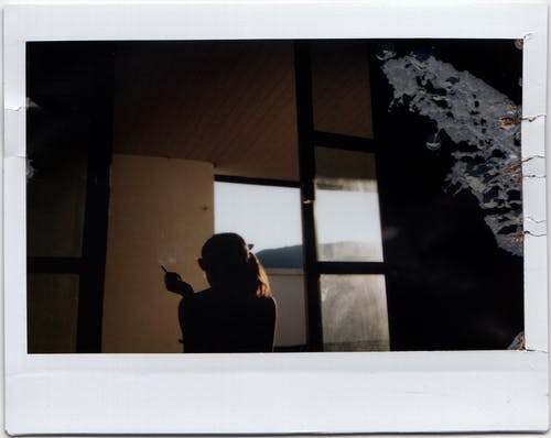 Silhouette of anonymous female sitting alone in dark room during sunset and smoking cigarette