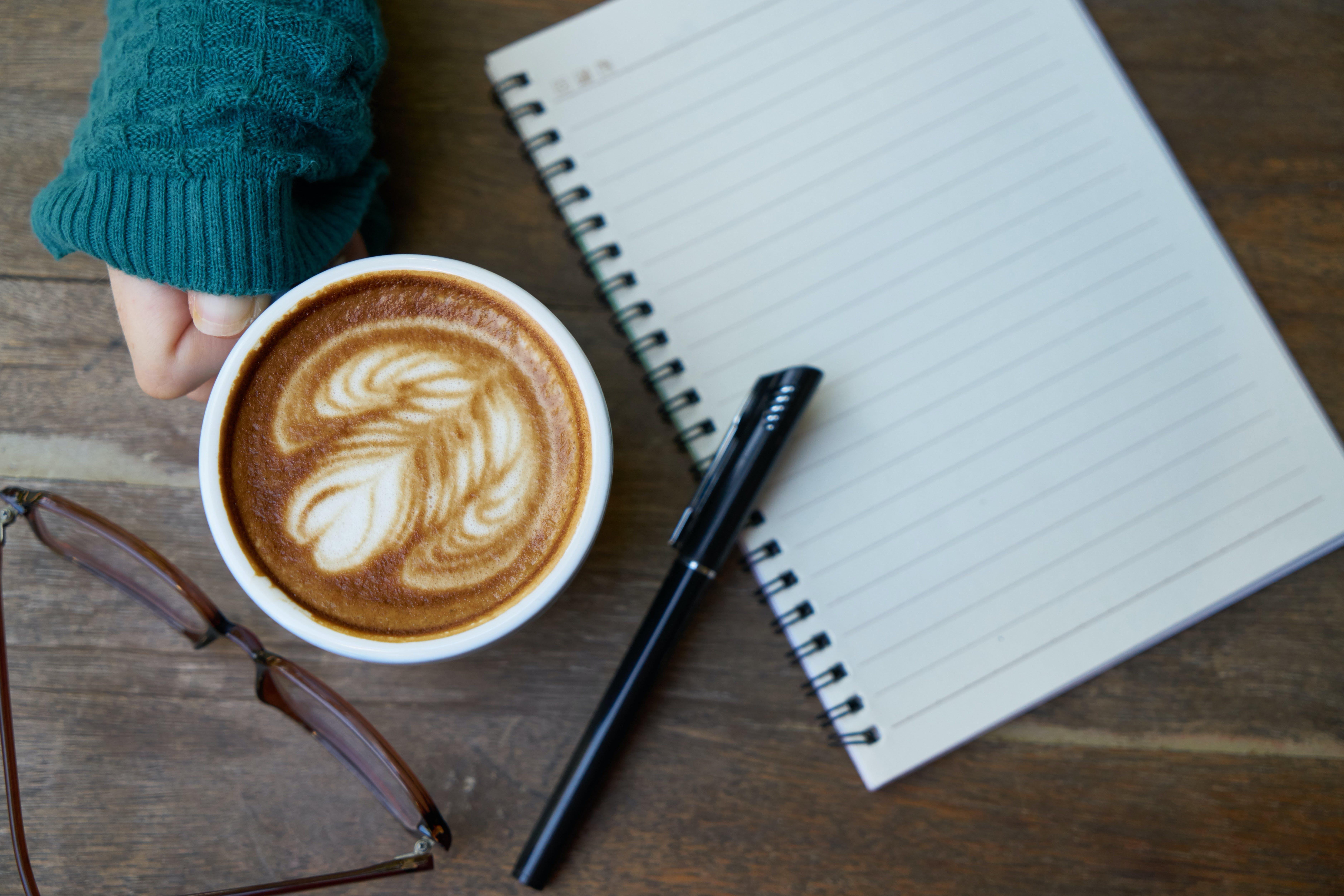 White Ceramic Mug Beside Ballpoint Pen