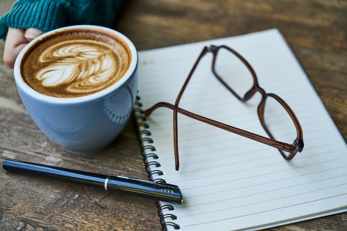 Brown Eyeglasses on White Notebook