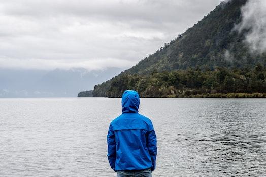 Person Wearing Blue Hoodie Near Body of Water