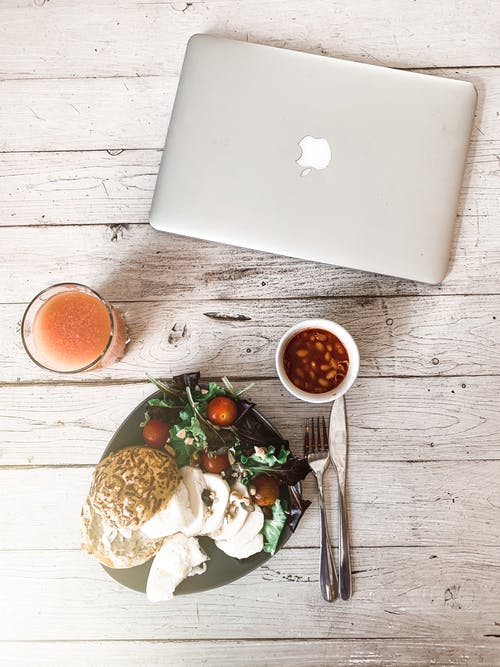 From above of plate with fresh salad and beans in tomato sauce placed near juice in glass and modern laptop