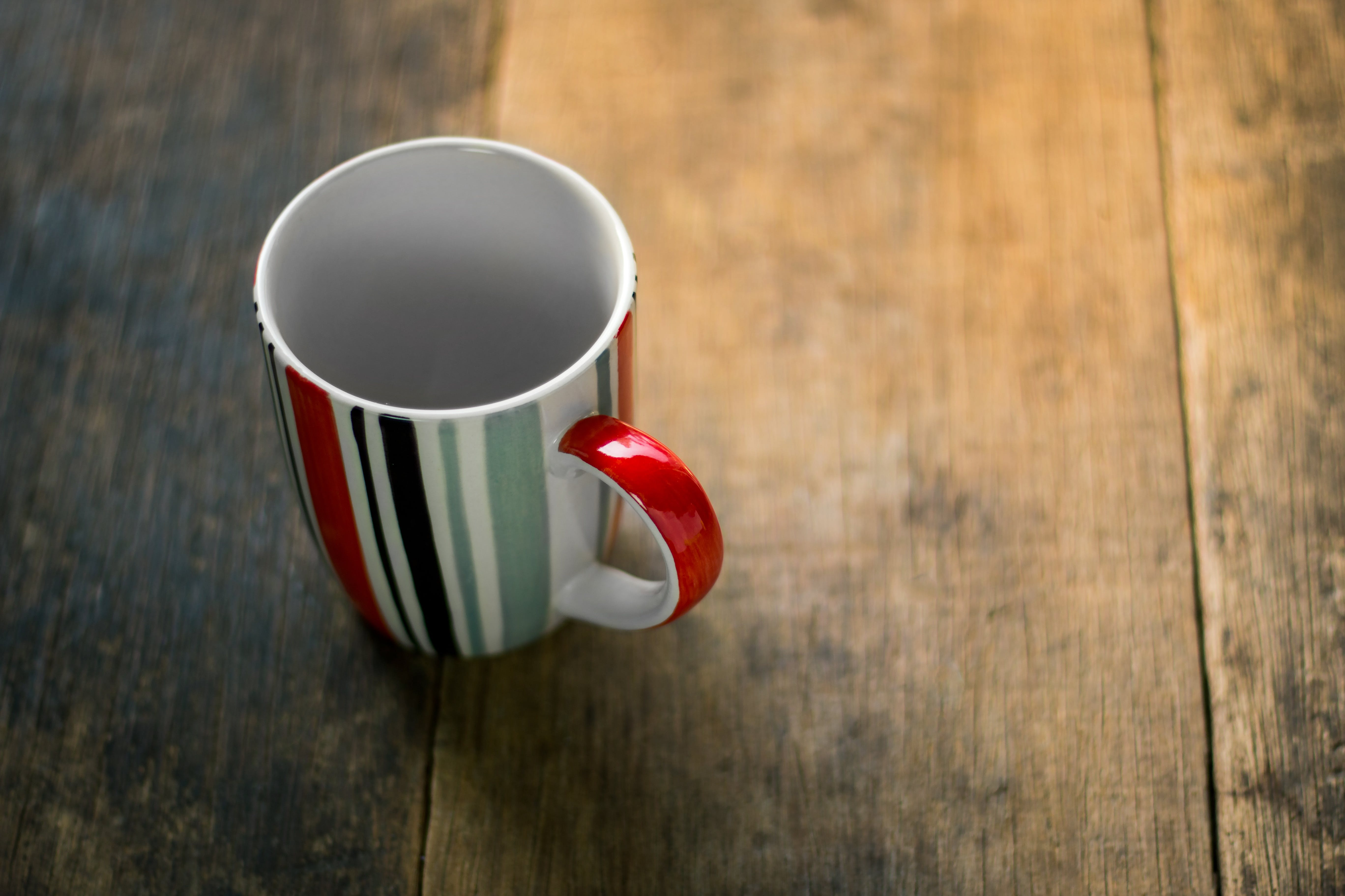 Red and White Striped Ceramic Mug on Brown Surface