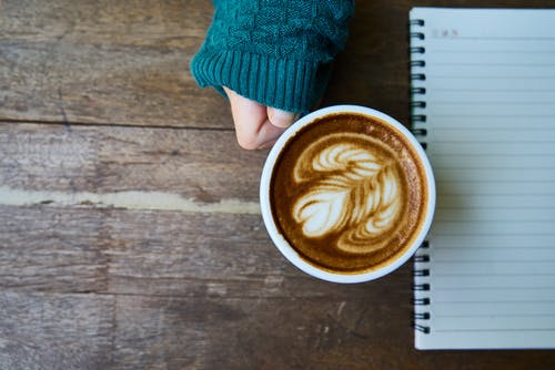Person Holding Cup of Coffee Beside Notebook
