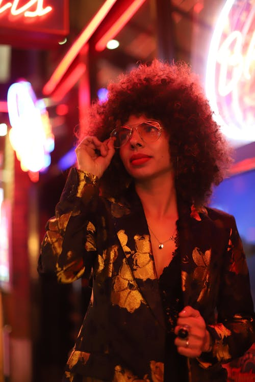 Stylish young female in sunglasses and elegant jacket standing against bright illuminated neon sign