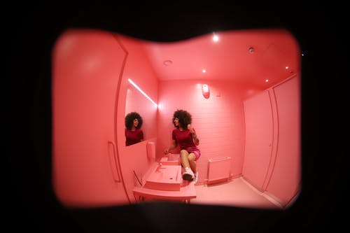 Wide angle full body of young female in pink dress sitting on sink in bright colorful restroom