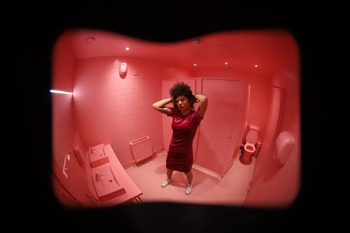 Wide angle full length of female with hands behind head standing in pink toilet