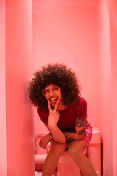 Positive young female with afro hairdo sitting on toilet and showing tongue and peace sign