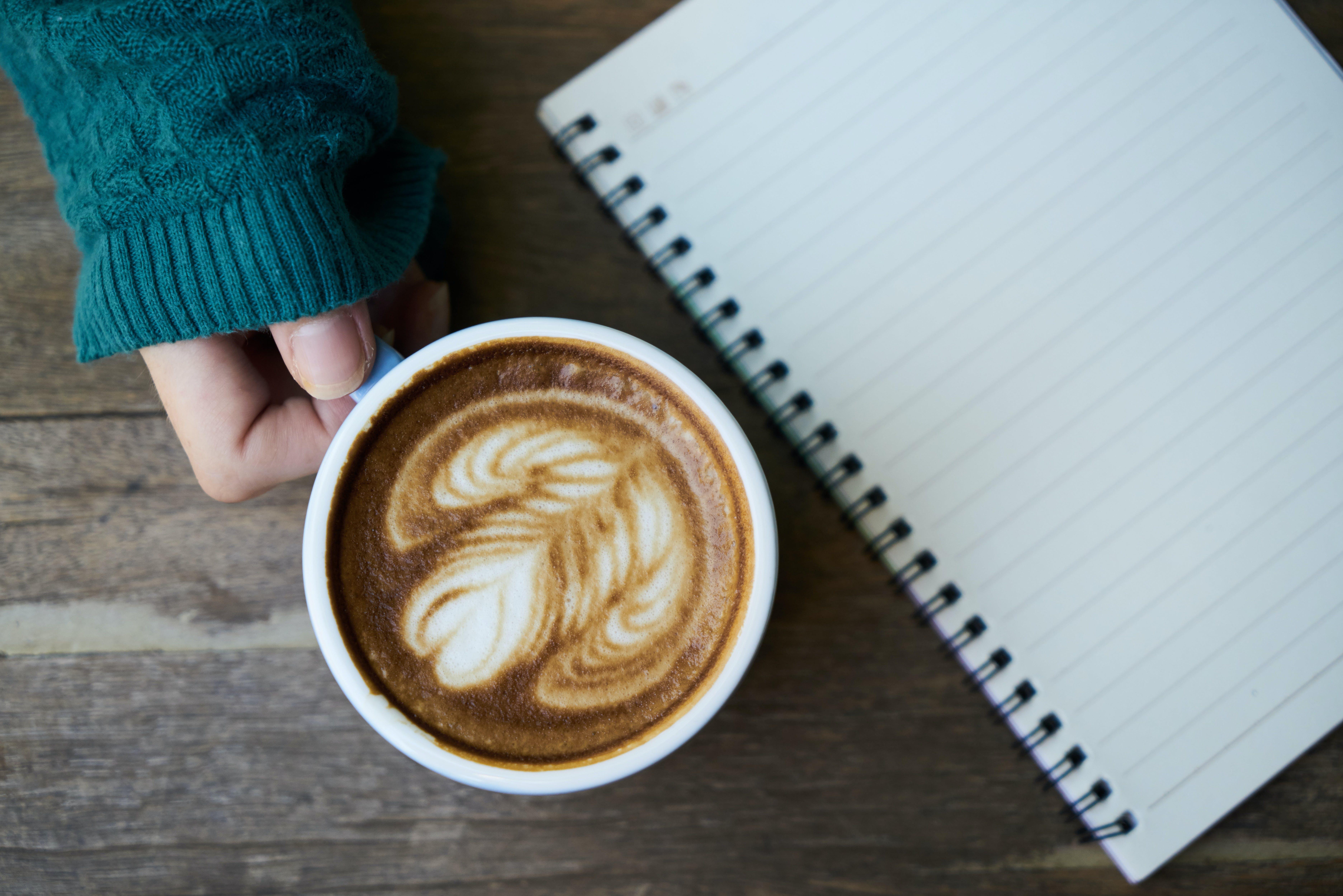 Person Holding White Ceramic Mug Beside Notebook