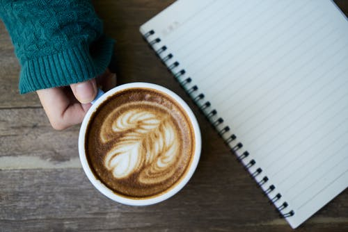 Person Holding White Ceramic Mug Beside Notebook
