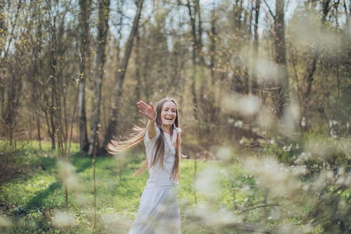 Happy woman spinning around in forest