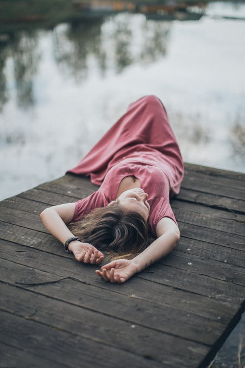 Woman in Pink Dress Lying on Brown Wooden Dock