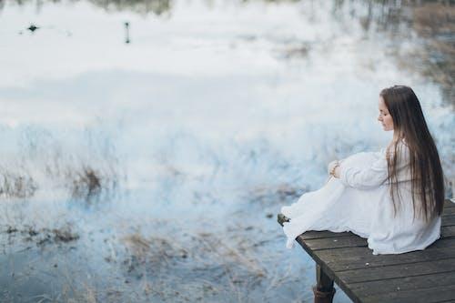 Side view of peaceful young female wearing elegant dress sitting on wooden boardwalk near lake