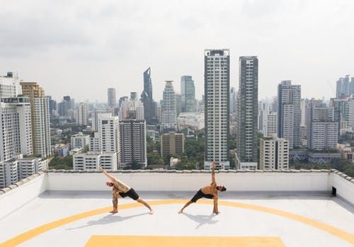 Flexible sportsmen practicing yoga on roof
