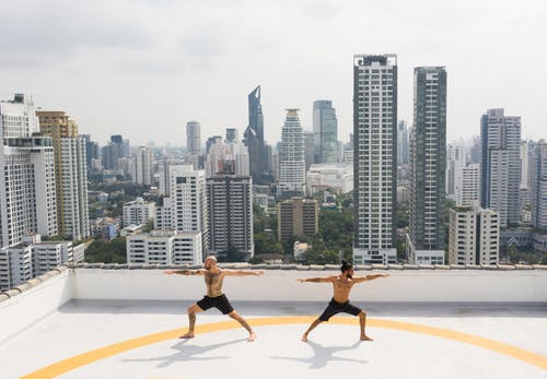 Strong sportsmen practicing yoga on rooftop in megapolis