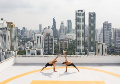 From above full length shirtless fit sportsmen performing triangle pose while practicing yoga together on rooftop against urban cityscape in daytime