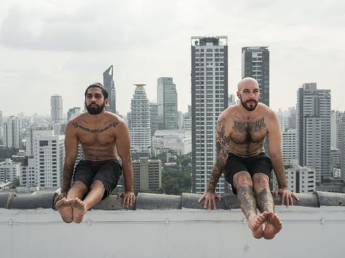 Full body bearded shirtless ethnic males with tattoos performing celibate pose while doing arm balance exercise and practicing yoga on roof against megapolis cityscape in daylight
