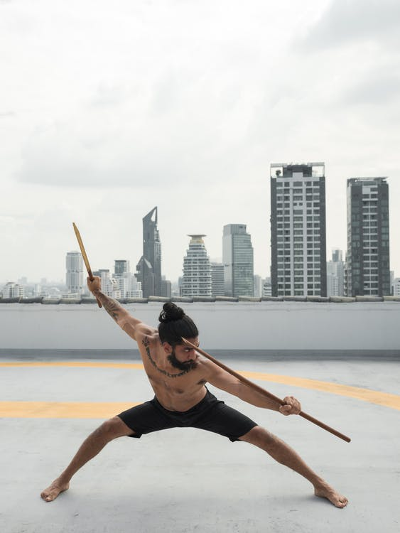 Photo of Man Holding Two Sticks