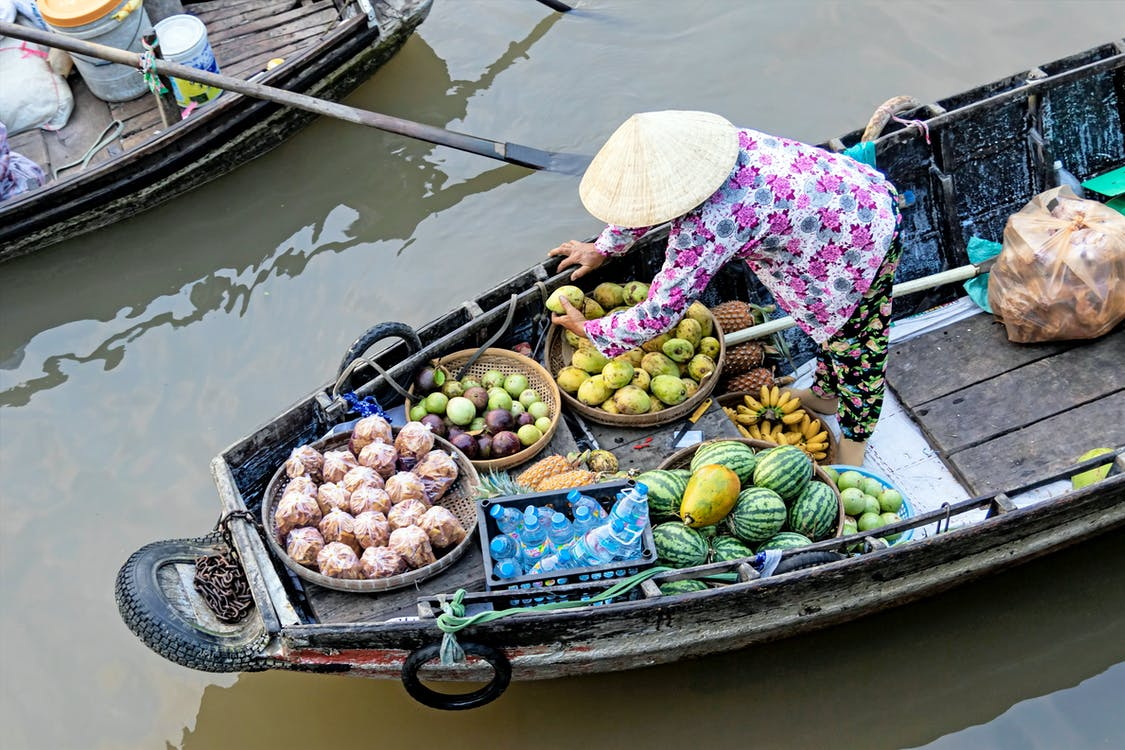 Photo of Person Selling Fruits While Standing on Boat