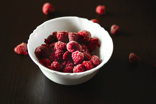 Raspberry on White Ceramic Bowl