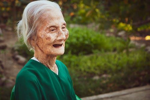 Senior woman with gray hair in green garden