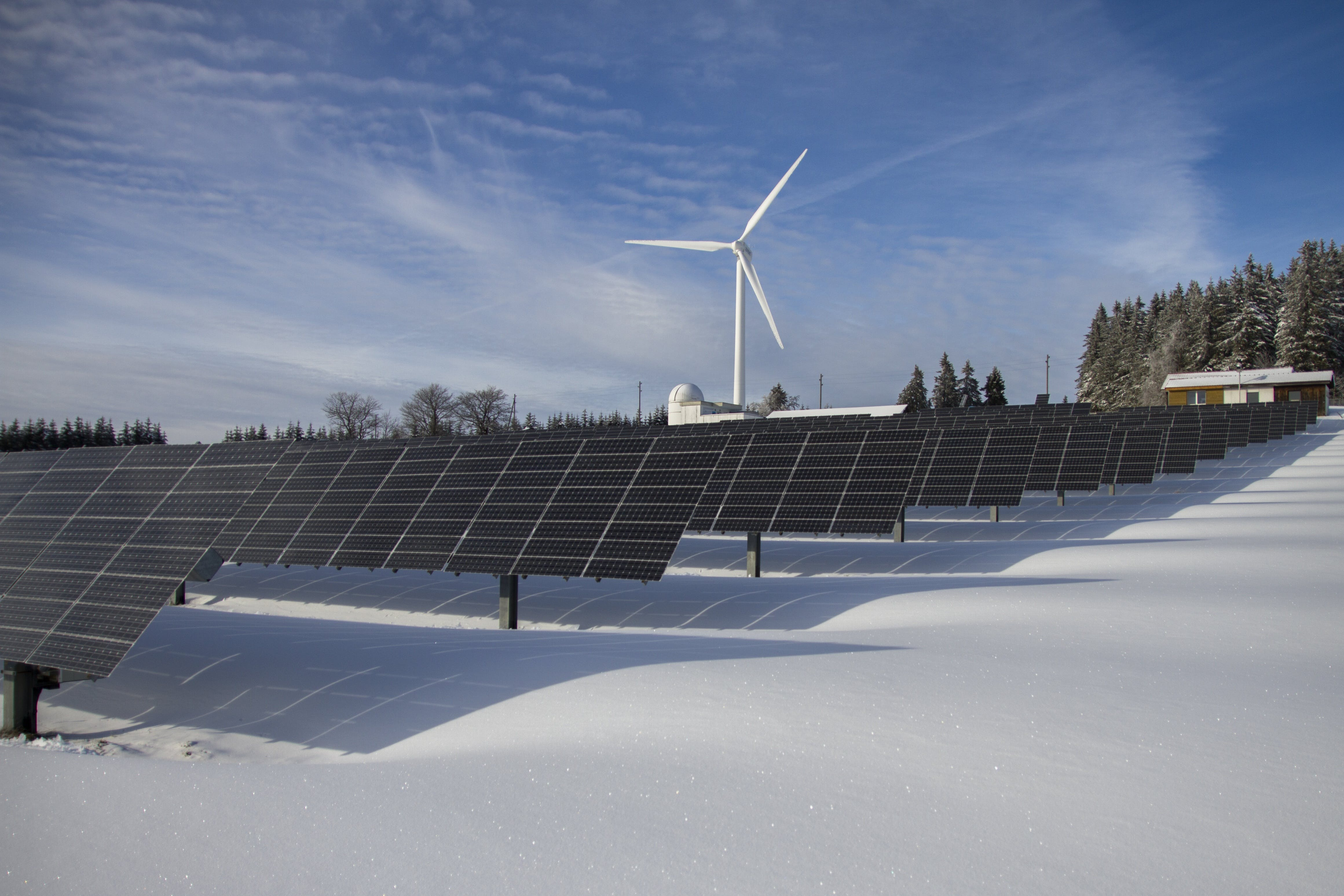 Solar Panels on Snow With Windmill Under Clear Day Sky
