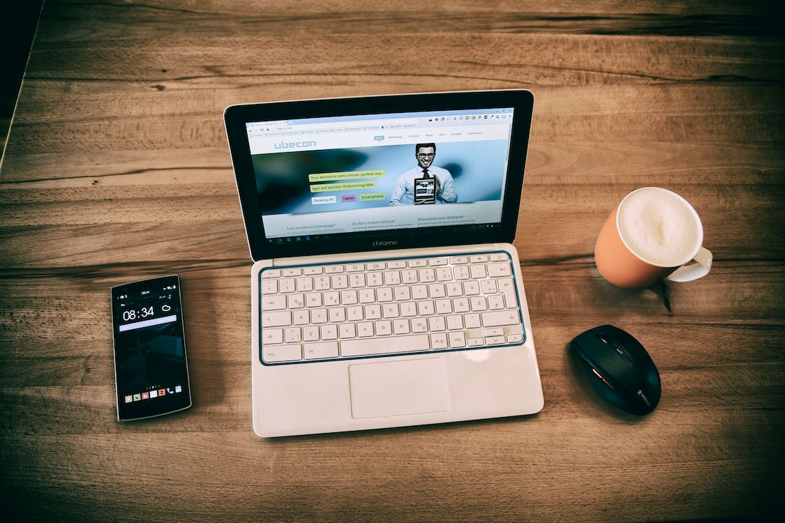 White and Black Laptop Computer Beside Cup and Smartphone