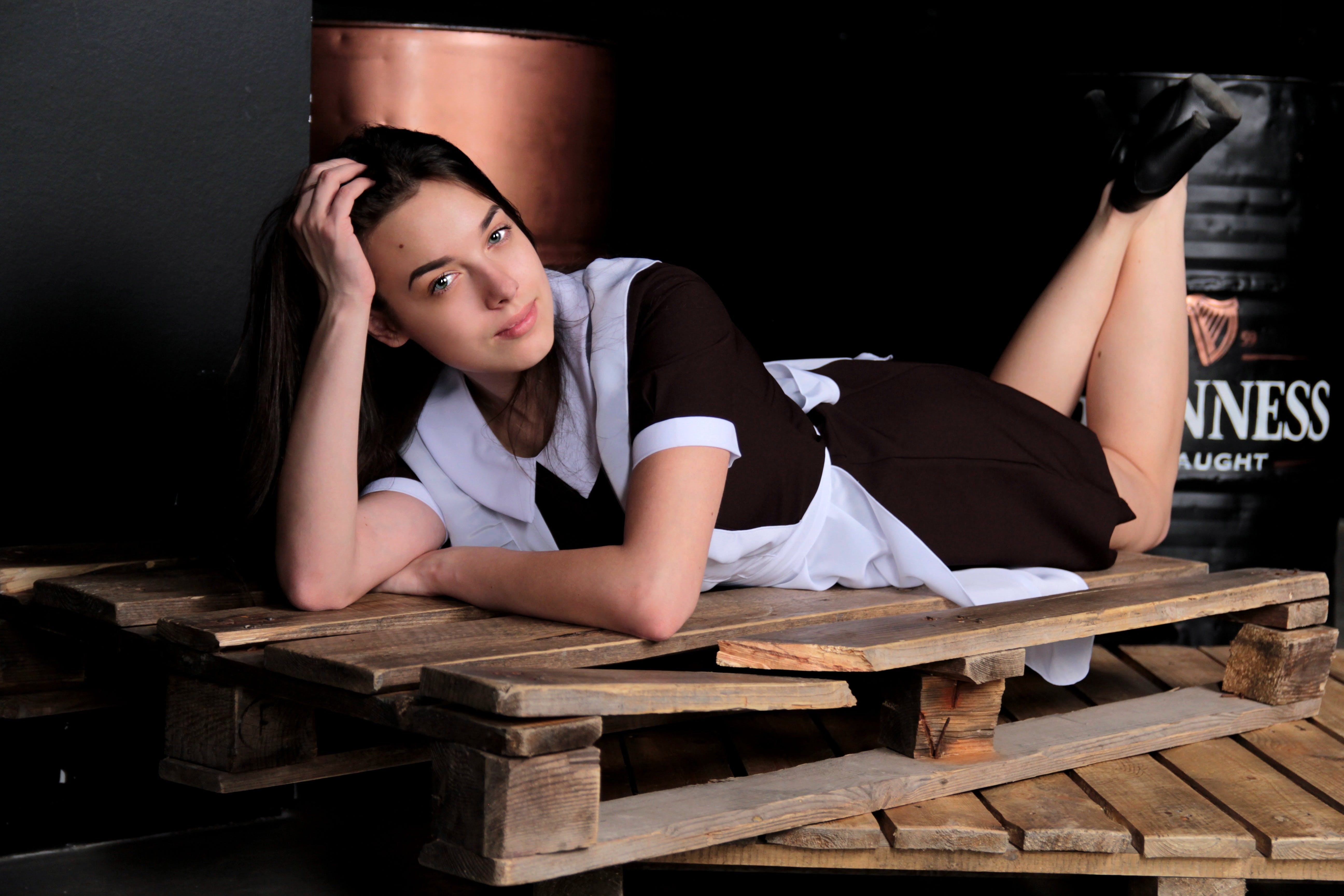 Woman in Maid Dress Lying on Pallet