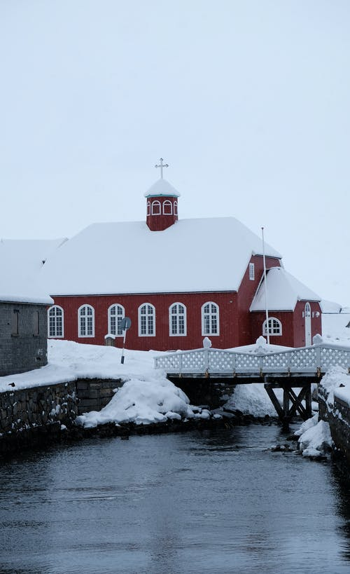 Church building covered with snow located on shore of cold river near bridge in winter