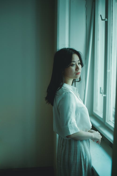 Side view of sad young Asian female in white dress standing near window and looking away at home