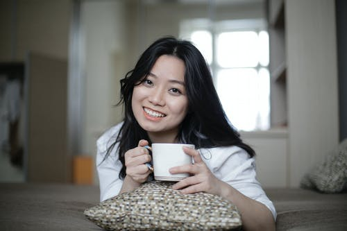 Cheerful Asian woman resting on bed in morning