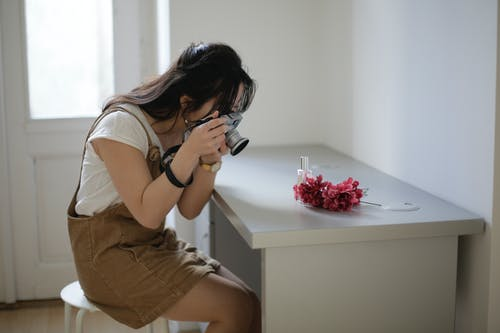 Asian woman taking pictures of flowers and perfume