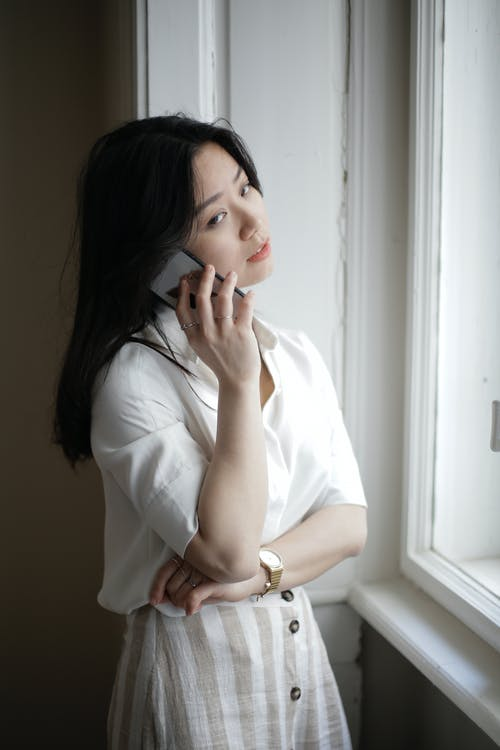 Young Asian woman speaking on smartphone near window