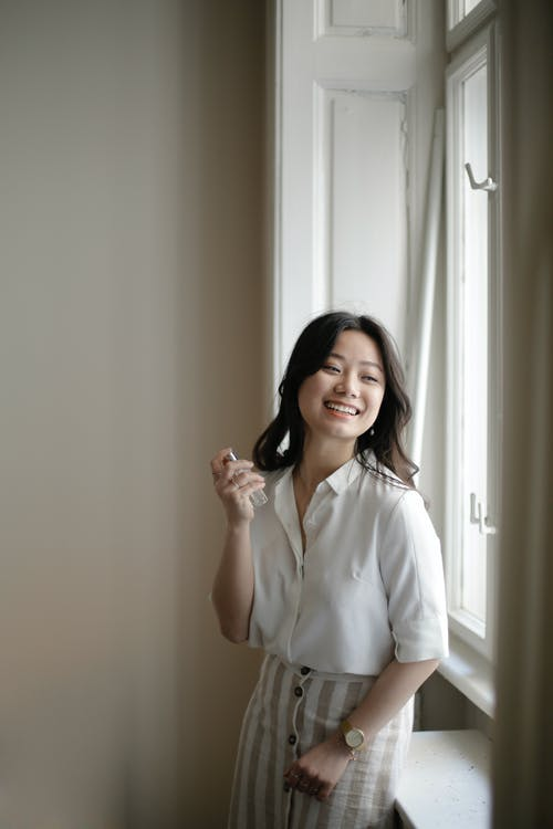 Cheerful Asian female applying perfume near window