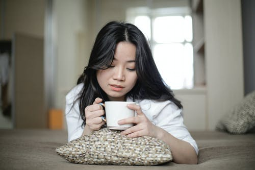 Young Asian woman with mug resting on bed