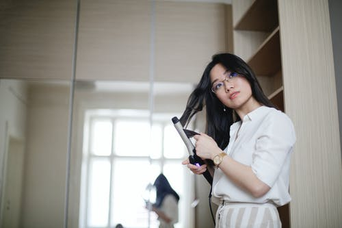 Low angle of stylish Asian female curling hair with iron and looking away in morning at home