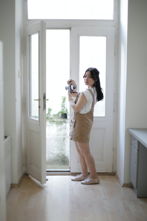 Side view of young Asian woman taking pictures of street form behind open door while standing in cozy room at home