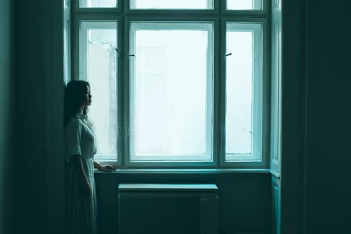 Side view of sad and lonely young Asian woman standing near window in gray room