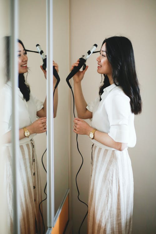 Side view of happy Asian female smiling and looking at mirror while coiling hair in morning at home