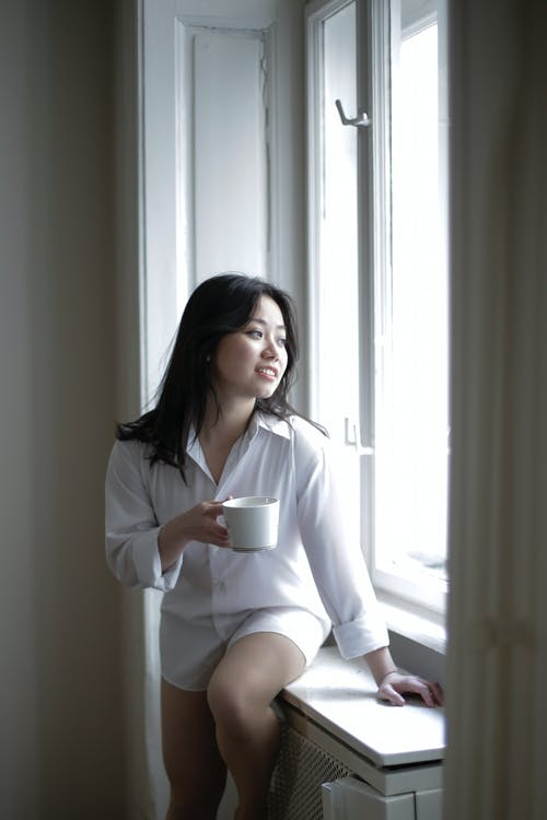 Young Asian woman with mug resting near window