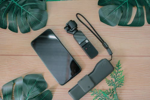 Top view composition of mobile phone placed near USB flash drive and mini gimbal camera on wooden table with green foliage