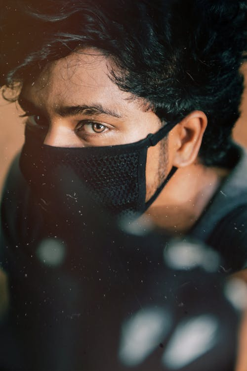 Serious young bearded male with black hair in black protective mask for coronavirus prevention looking at camera