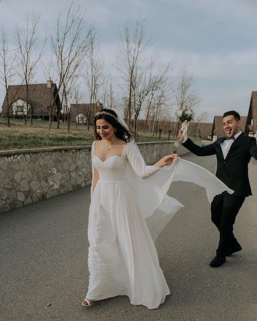 Happy newlywed couple walking on street