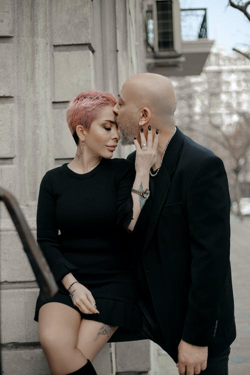 Stylish adult bald man kissing elegant sensual woman on forehead while having romantic moment near old gray building on city street