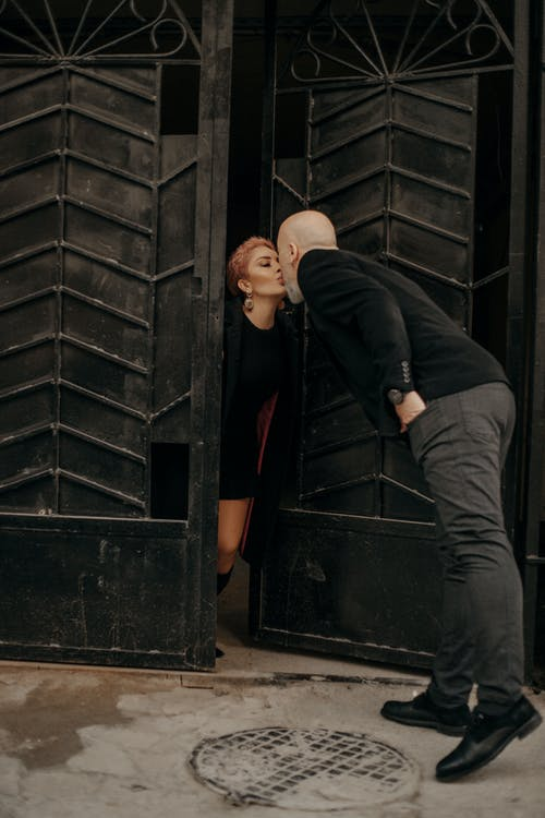 Adult romantic couple kissing in doorway
