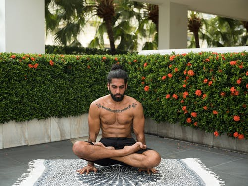 Photo of Man in Black Shorts Doing Yoga
